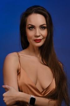 明るい化粧と金色のシルクのドレスを着たセクシーなデコルテと青い壁にポーズをとってスマートな時計の笑顔を持つブルネットの女性