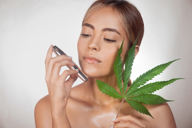 自然な治療のために大麻抽出物から作られたcbdブラックマスカラを持つブルネットの女性。灰色の背景に分離