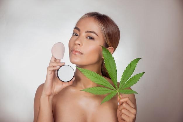 自然なメイクアップのための大麻抽出物から作られたcbdスキンパウダーを持つブルネットの女性。灰色の背景に分離