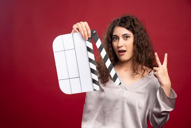 그녀의 두 손가락을 보여주는 clapperboard와 갈색 머리 여자.