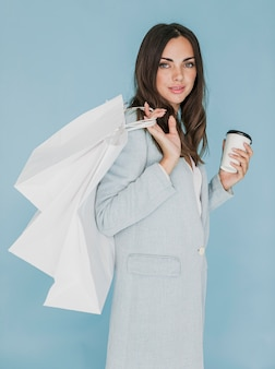 Brunette woman with coffee and shopping bags on shoulder