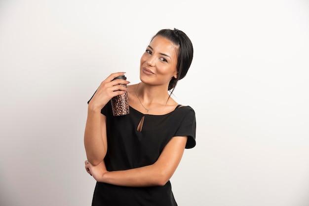 Donna castana con la tazza di caffè che sorride sulla parete bianca.