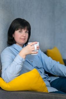 カップを持つブルネットの女性は、自宅のソファでリラックスしています。昼休みに休んでいるビジネスウーマン。垂直フレーム。