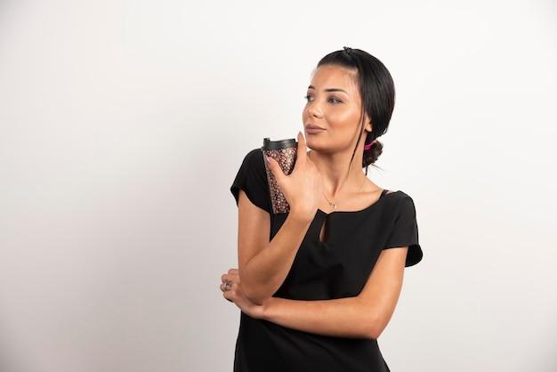 白い壁に立っているコーヒーのカップを持つブルネットの女性。