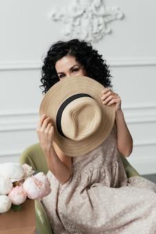巻き毛のブルネットの女性は椅子に座っている間麦わら帽子の後ろに彼女の顔を隠します