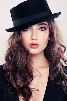 Brunette woman with curly hairstyle and black hat
