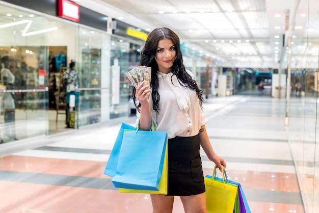 쇼핑하는 달러 팬을 가진 갈색 머리 여자