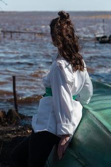 湖を見て、ボートに寄りかかって髪のお団子スタイルのブルネットの女性