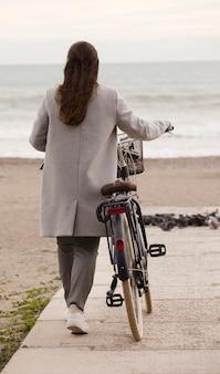 Брюнетка женщина со своим велосипедом зимой, гуляя вдоль побережья вдоль морского пляжа.