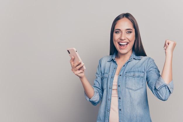 Брюнетка женщина с джинсовой курткой держит ее телефон