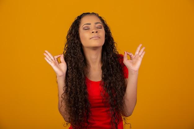 長くて光沢のある巻き毛の祈りとブルネットの女性