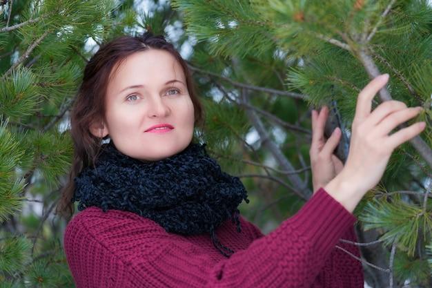 긴 머리와 갈색 눈을 가진 갈색 머리 여자는 갈색 스웨터를 입고 소나무 숲에 서 있는 목에 검은 스카프를 두르고 있습니다.