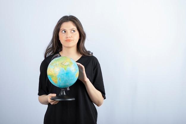 긴 머리를 가진 갈색 머리 여자는 세계 여행 장소를 선택합니다.