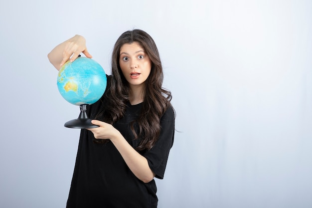 Brunette woman with long hair holding world globe and posing .