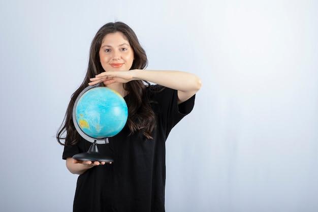 Donna castana con capelli lunghi che tiene globo del mondo e posa.