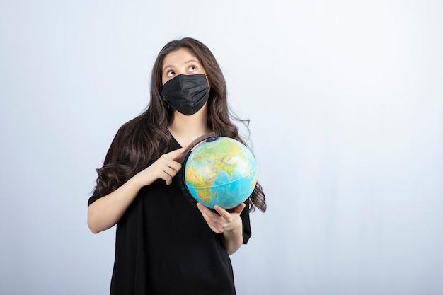 세계 지구본을 들고 의료 마스크에 긴 머리를 가진 갈색 머리 여자