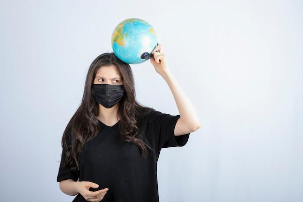 세계 지구본을 들고 의료 마스크에 긴 머리를 가진 갈색 머리 여자.