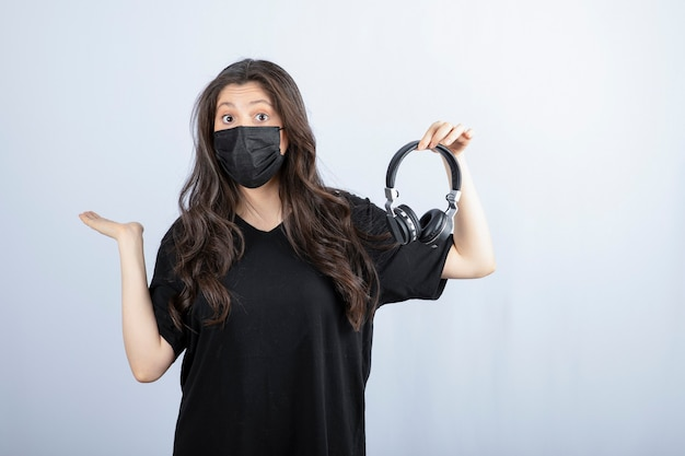 Donna castana con capelli lunghi nella mascherina medica che tiene le cuffie.