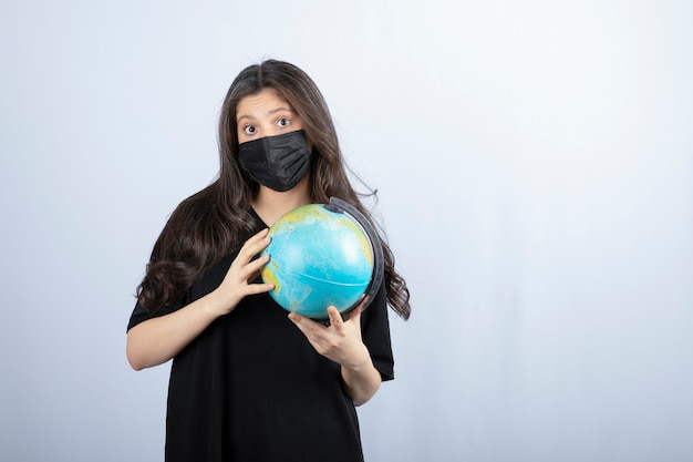 Brunette woman with long hair in medical mask holding world globe .
