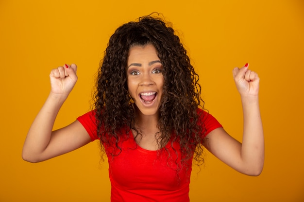Brunette woman with long and shiny curly hair celebrating