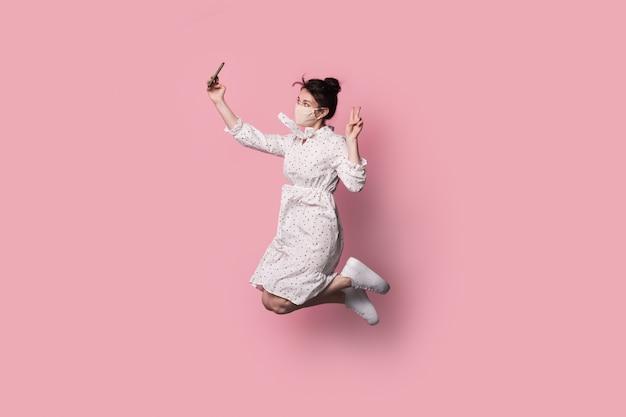 顔に医療マスクを持つブルネットの女性は、夏のドレスでジャンプし、ピンクのスタジオの壁に自分撮りを作っています