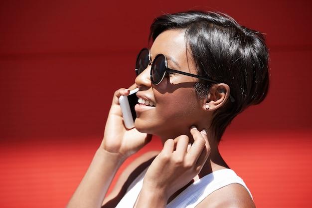 電話で話しているピクシーの髪型を持つブルネットの女性