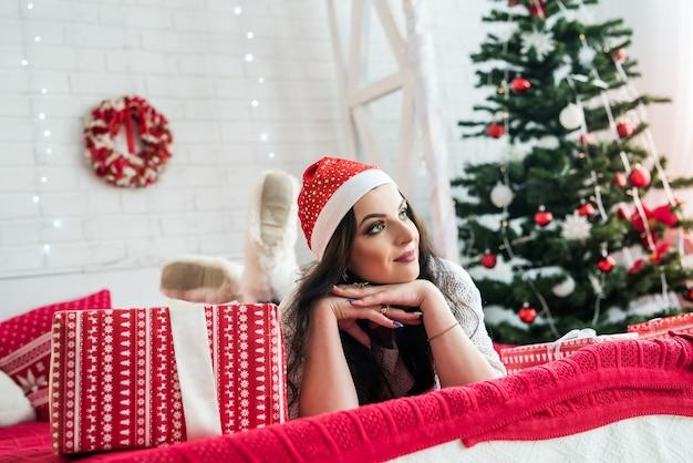 ベッドに横たわっているプレゼントボックスを持つブルネットの女性