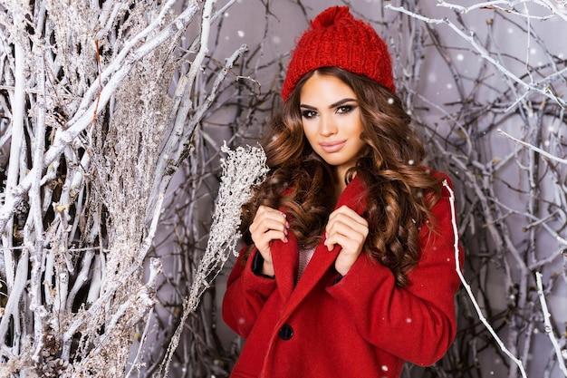 Donna castana con vestiti rossi tra alberi innevati