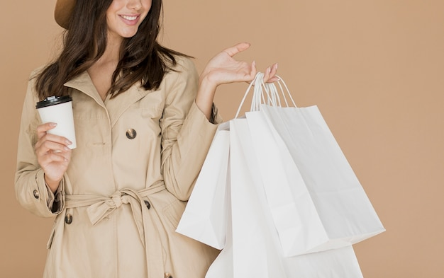 Brunette woman with shopping bags and coffee