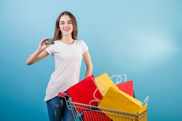 Brunette woman with shopping cart full of colorful paper bags and credit card isolated over blue