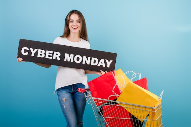 Brunette woman with shopping cart full of colorful red and yellow paper bags and cyber monday sign isolated over blue