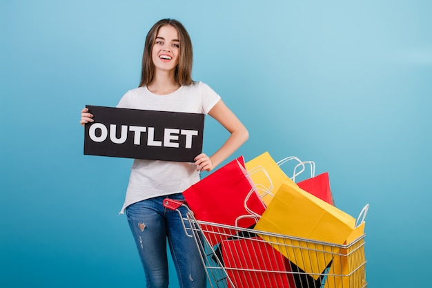 Brunette woman with shopping cart full of colorful red and yellow paper bags and outlet sign isolated over blue