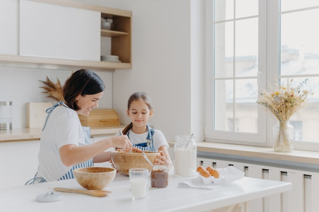 Brunette woman with smile shows little daughter how to cook