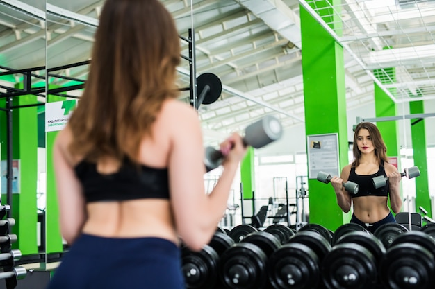 Brunette woman with strong fit body is doing different exercises in modern sportclub with mirrors