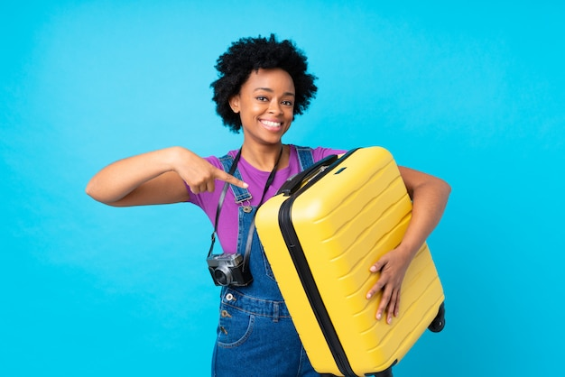 Brunette woman with suitcase over isolated blue background