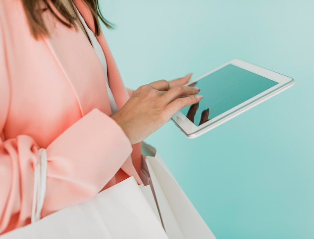 Brunette woman with tablet and shopping bags