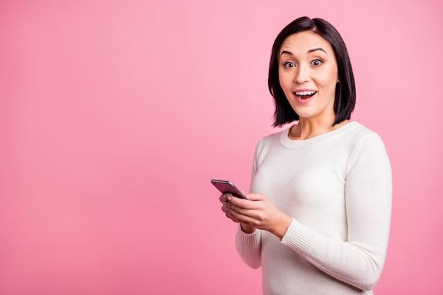Брюнетка женщина с белым пуловером держит свой телефон, изолированные на розовом