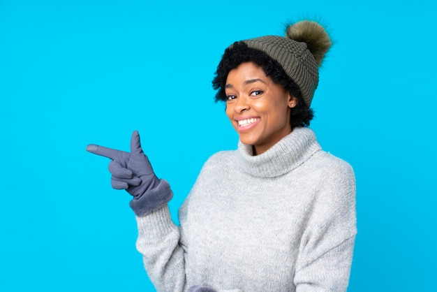 Brunette woman with winter hat over isolated blue background