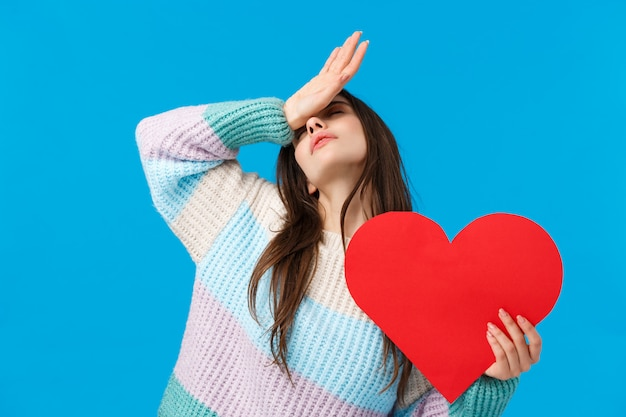 Brunette woman with winter sweater holding red heart