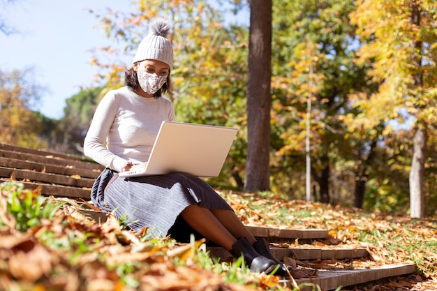 Brunette woman working with her laptop outdoors.