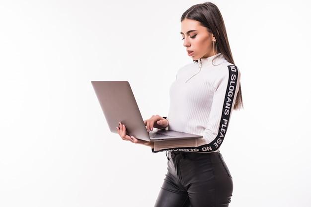 La donna castana lavora al suo computer portatile isolato