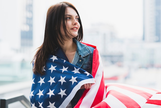 Brunette woman wrapped in american flag on background of city