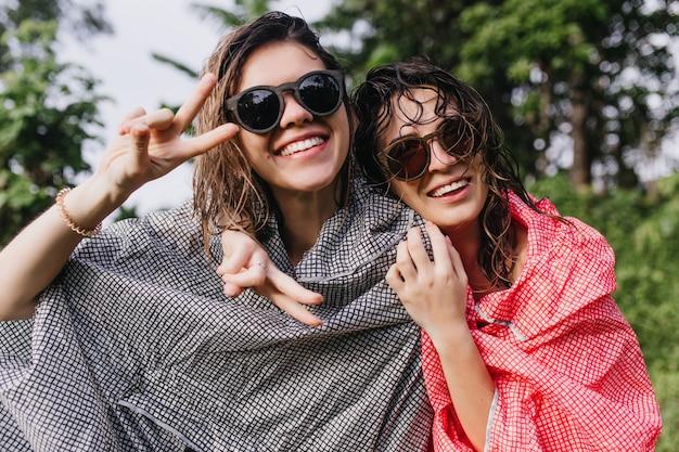 그녀의 여동생을 껴안은 우비에 갈색 머리 여자. 자연에 포즈를 취하는 선글라스에 두 즐거운 친구의 야외 사진.
