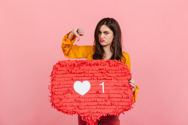 Brunette in yellow blouse posing displeased with thumb down, denouncing likes on social networks.