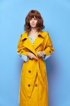 ブルネットの黄色いコートは短い髪のスタイリッシュな服のクローズアップで横に見えます