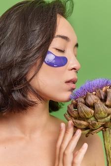 갈색 머리의 젊은 아시아 여성은 눈 아래 파란색 패치를 적용하고 꽃은 눈을 감고 셔츠를 입지 않은 채 녹색 벽에 격리된 미용 절차를 받습니다.