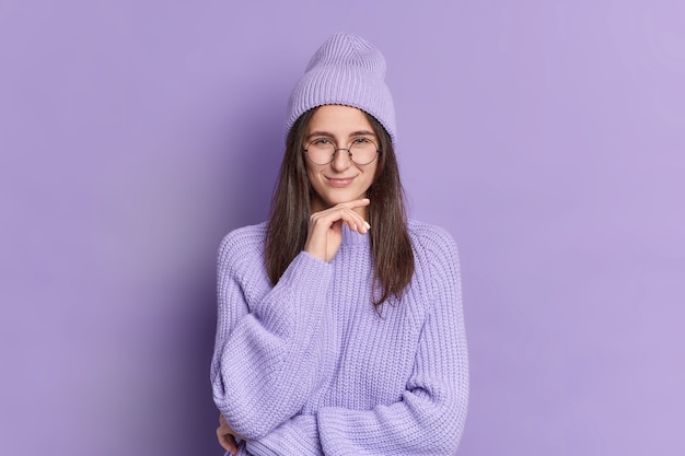 Brunette young beautiful woman holds chin and has sly expression tricky plan smiles pleasantly wears fashionable hat knitted sweater