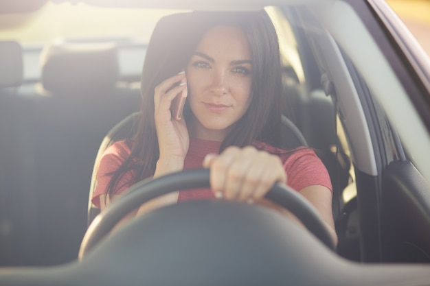 Brunette young female driver speaks via modern cell phone while driving car, has serious exression