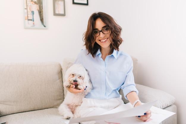 Una giovane ragazza bruna con una camicia blu è seduta sul divano in studio. abbraccia il cagnolino bianco e tiene alcuni schizzi sulle ginocchia. sta sorridendo alla telecamera.