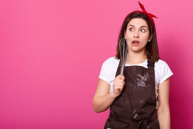 小麦粉を塗った茶色のエプロンのブルネットの若い女性